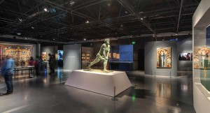 View of ther Eretz Irael Museum exhibit. The sculpture of the musclebound Bar Kokhba in the center is by 20th-century sculptor Chanoch Glicenstein. Courtesy Eretz Israel Museum, Tel Aviv.