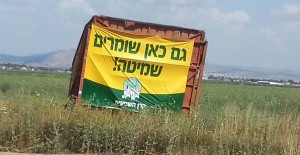 "The sign reads: ""Here we also keep the Sabbath of the Land"" Mount Gilboa is in the background. Photo: Miriam Feinberg Vamosh"